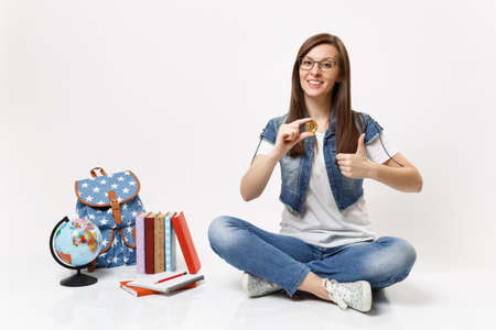 Young attractive woman student in glasses holding bitcoin showing tumb up sitting near globe, backpack, school books isolated on white background. Education in high school university college concept Stock Photo