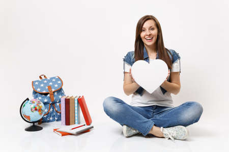 Young amazed exited woman student holding white heart with copy space and sitting near globe, backpack, school books isolated on white background. Education in high school university college concept