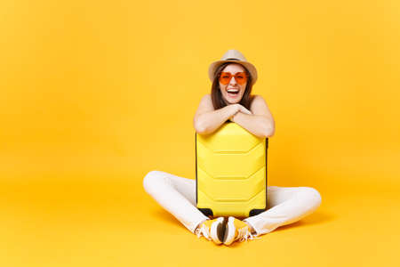 Traveler tourist woman in summer casual clothes, hat sit with suitcase isolated on yellow orange background. Female passenger traveling abroad to travel on weekends getaway. Air journey concept