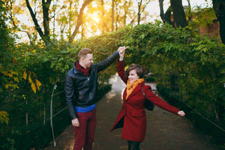 Young happy couple in love, attractive happy woman and man in casual warm clothes dancing and whirling walking near green arch in autumn city park outdoors. Love relationship family lifestyle concept 免版税图像