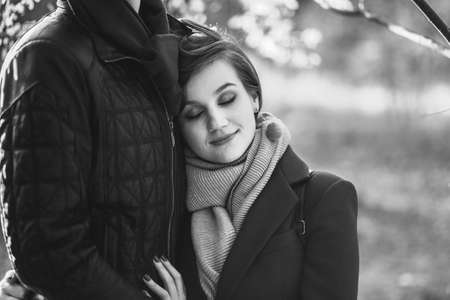 Portrait of Young beautiful woman with closed eyes leaning on man in casual clothes embracing hugging on walk in autumn city park outdoors. Love relationship family people concept. Black and white
