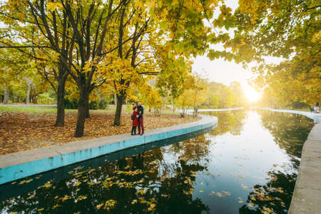 Young romantic couple in love woman and man in casual warm clothes holding hands embracing hugging standing near water in autumn city park outdoors. Love relationship family people lifestyle concept 免版税图像