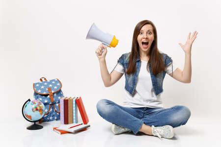 Young amazed woman student in denim clothes spreading hands holding megaphone sitting near globe backpack school book isolated on white background. Education in high school university college concept