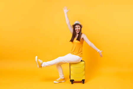 Traveler tourist woman in summer casual clothes, hat sit on suitcase isolated on yellow orange background. Female passenger traveling abroad to travel on weekends getaway. Air flight journey concept