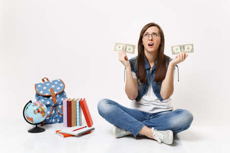 Young exhausted woman student looking up holding dollar bills have problem with money sit near globe, backpack, school books isolated on white background. Education in high school university college