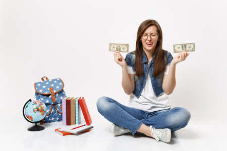 Young upset woman student crying holding dollar bills cash money have financial problem sit near globe, backpack school books isolated on white background. Education in high school university college Stock Photo