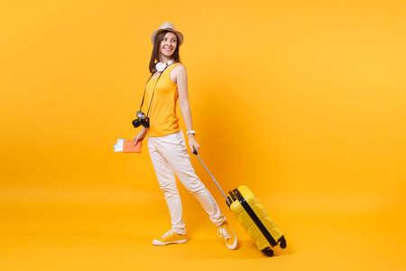 Turystyczna kobieta podróżnik w letnie ubranie, kapelusz ze słuchawkami na szyi na białym tle na żółtym pomarańczowym tle. Pasażer wyjeżdżający za granicę w celu wyjazdu na weekendowy wypad. Koncepcja podróży lotem lotniczym