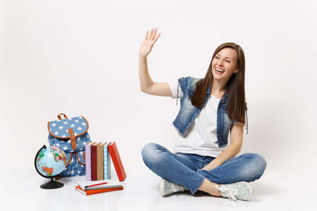Portrait of happy laughing woman in denim clothes student waving hand for greeting sitting near globe, backpack school books isolated on white background. Education in high school university college Stock Photo