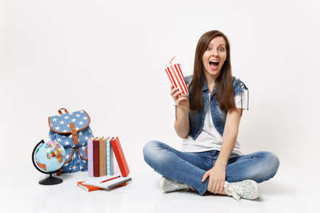 Young exited woman student with opened mouth holding plastic cup of soda or cola sitting near globe, backpack, school books isolated on white background. Education in high school university college