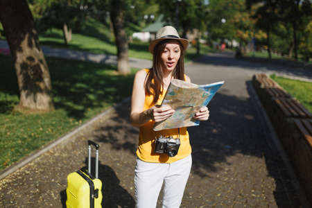 Shocked traveler tourist woman in yellow summer casual clothes, hat with suitcase looking on city map in city outdoor. Girl traveling abroad to travel on weekends getaway. Tourism journey lifestyle