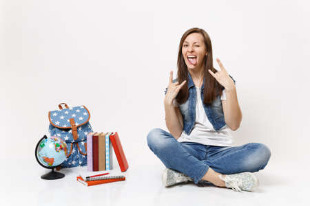 Portrait of young crazy funny woman student showing tongue rock-n-roll sign sitting near globe backpack, school books isolated on white background. Education in high school university college concept