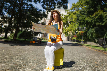 Puzzled traveler tourist woman in casual clothes, hat sitting on suitcase holding city map search route in city outdoor. Girl traveling abroad to travel on weekend getaway. Tourism journey lifestyle