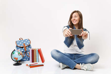 Young smiling woman student doing taking selfie shot on mobile phone looking aside sitting near globe, backpack, school books isolated on white background. Education in high school university college 版權商用圖片