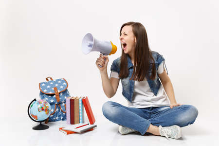 Young crazy casual woman student in denim clothes screaming holding megaphone sitting near globe backpack school book isolated on white background. Education in high school university college concept Stok Fotoğraf - 107557265