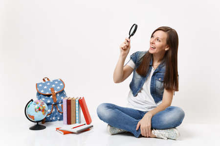 Young laughing pretty woman student holding looking on magnifying glass sitting near globe, backpack, school books isolated on white background. Education in high school university college concept Stock Photo