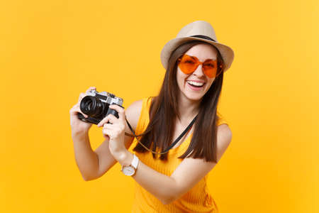 Tourist woman in summer casual clothes, hat take picture on retro vintage photo camera isolated on yellow background. Girl traveling abroad to travel on weekends getaway. Air flight journey concept