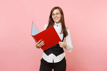 Young successful business woman in glasses holding red folder for papers document and showing thumb up isolated on pink background. Lady boss. Achievement career wealth. Copy space for advertisement