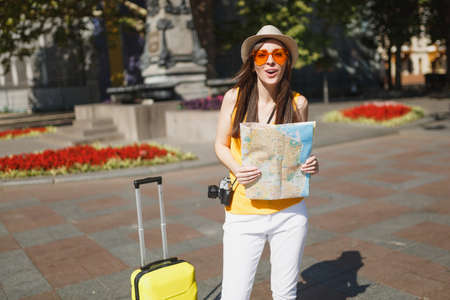 Cheerful traveler tourist woman in hat, yellow clothes, orange heart glasses with suitcase hold city map in city outdoor. Girl traveling abroad to travel on weekend getaway. Tourism journey lifestyle