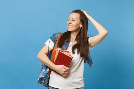 Portrait of young cheerful woman student with backpack touching and correct hairstyle looking aside, hold school books isolated on blue background. Education in high school university college concept