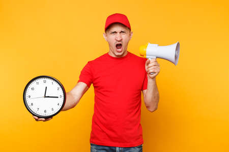 Delivery service man in red uniform isolated on yellow background. Male employee courier in cap, t-shirt scream in megaphone hold clock. Guy announces discounts sale Copy space advertisement Hurry up