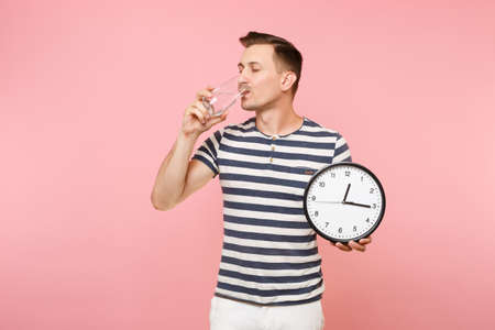 Portrait of happy caucasian man in striped t-shirt holding round clock, drinking clear fresh pure water from glass isolated on trending pastel pink background. People time healthy lifestyle concept 版權商用圖片 - 107586261