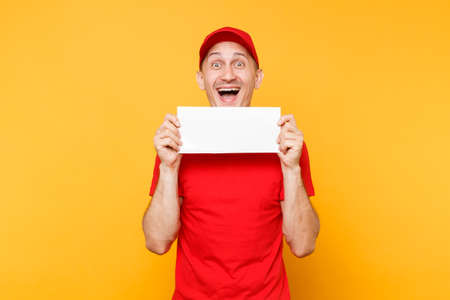 Delivery man in red uniform isolated on yellow orange background. Professional male employee courier in cap, t-shirt hold white empty blank paper. Service concept. Copy space place for text or image