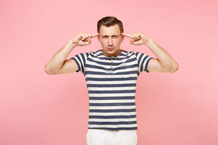 Portrait of pensive young man in striped t-shirt thinking, put index fingers on temple face copy space isolated on trending pink background. People sincere emotions lifestyle concept. Advertising