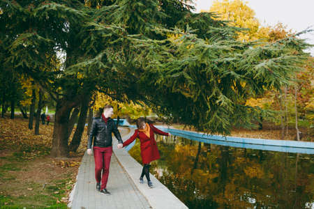 Young joyful couple in love woman and man in warm clothes holding hands having fun walking on road near water? coniferous trees in autumn city park outdoors. Love relationship family people lifestyle 版權商用圖片