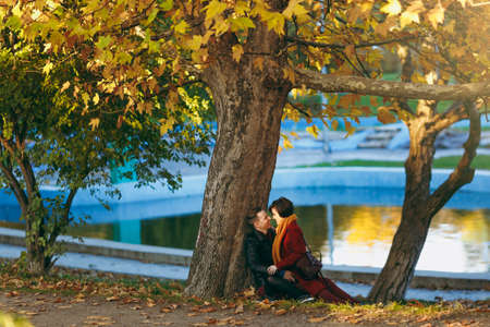 Young laughing happy couple in love woman and man looking at each other sitting on fallen leaves near tree and water in autumn city park outdoors. Love relationship family people lifestyle concept 免版税图像