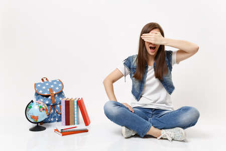 Portrait of young casual woman student screaming covering face with hand and sitting near globe backpack school books isolated on white background. Education in high school university college concept