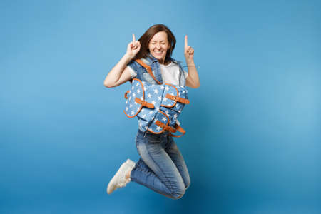Full length portrait young overjoyed woman student with closed eyes with backpack jumping pointing index figers up isolated on blue background. Education in high school. Copy space for advertisement Stock Photo