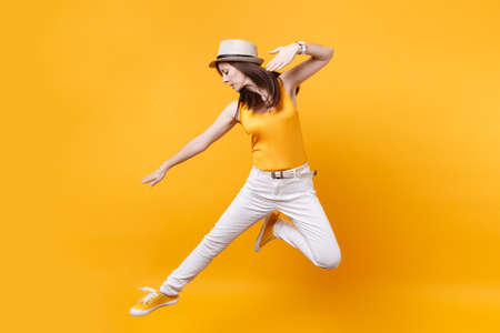 Portrait of excited smiling young happy jumping high woman in straw summer hat, copy space isolated on yellow orange background. People sincere emotions, passion lifestyle concept. Advertising area