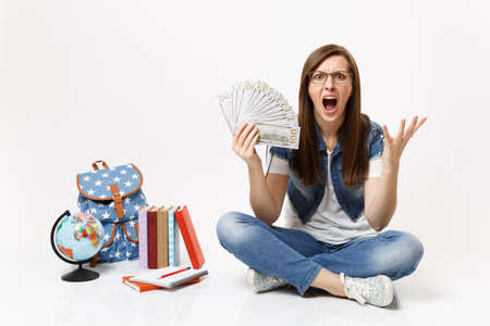 Young angry woman student screaming spreading hands holding bundle lots of dollars, cash money sit near globe backpack, books isolated on white background. Education in high school university college Banque d'images