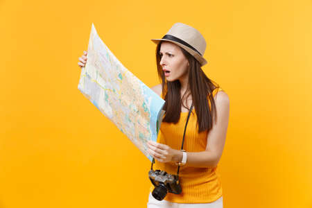 Puzzled traveler tourist woman in summer casual clothes, hat looking on city map isolated on yellow orange background. Female traveling abroad to travel on weekends getaway. Air journey concept Banque d'images - 108167559