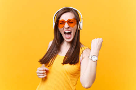 Portrait of excited fun girl in orange glasses listening music in headphones doing winner gesture, say Yes, copy space isolated on yellow background. People sincere emotions concept. Advertising area