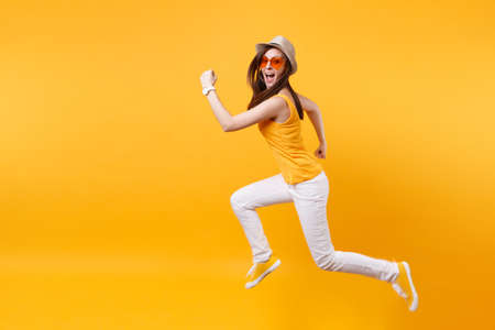 Portrait of excited smiling young jumping high woman in straw summer hat, orange glasses copy space isolated on yellow background. People sincere emotions, passion lifestyle concept. Advertising area Stock Photo