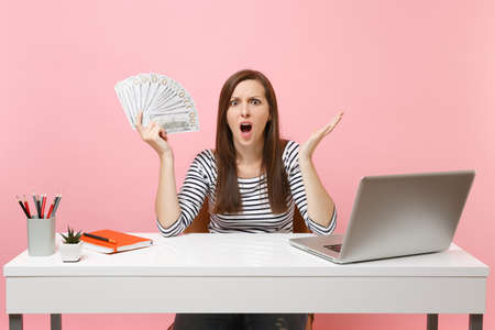 Young shocked bewildered woman spreading hands with bundle lots of dollars cash money work at office at white desk with pc laptop isolated on pink background. Achievement business career. Copy space Фото со стока