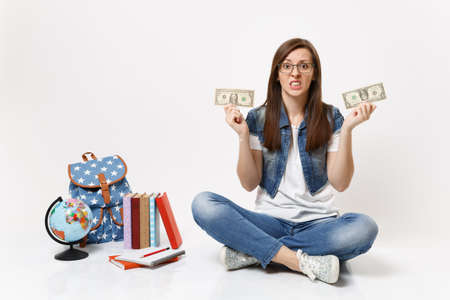 Young dissatisfied woman student hold dollar bills cash money feeling stressed by lack of money sit near globe backpack books isolated on white background. Education in high school university college