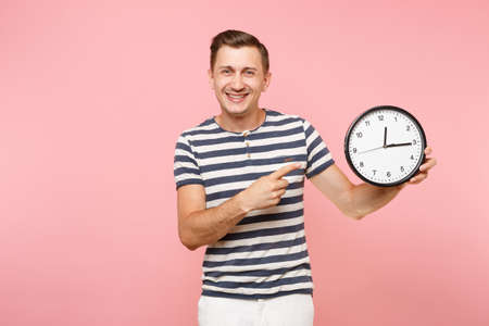 Portrait of smiling happy man wearing striped t-shirt holding round clock, copy space isolated on trending pastel pink background. People sincere emotions lifestyle concept. Time is running out