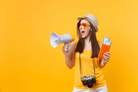 Expressive tourist woman in summer casual clothes hat holding megaphone passport tickets isolated on yellow orange background. Female traveling abroad to travel weekends getaway. Air flight concept