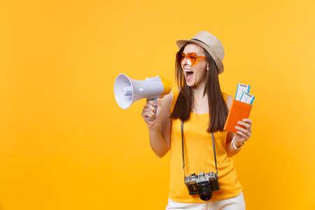 Femme touristique expressive en chapeau de vêtements décontractés d'été tenant des billets de passeport mégaphone isolés sur fond orange jaune. Femme voyageant à l'étranger pour une escapade de week-end. Concept de vol aérien Banque d'images