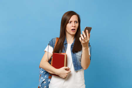 Young shocked puzzled woman student with backpack holding school books, looking on mobile phone after conversation isolated on blue background. Education in high school university college concept