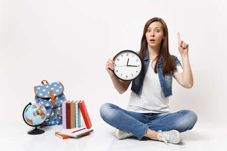 Young shocked woman student pointing index finger up holding alarm clock sitting near globe, backpack, school books isolated on white background. Education in high school university college concept