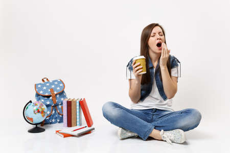 Young drowsy woman student holding paper cup with coffee or tea yawning want sleep sitting near globe, backpack, school books isolated on white background. Education in high school university college