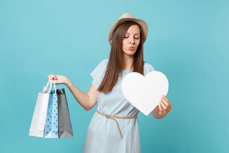 Portrait fashionable beautiful woman in summer dress, straw hat holding packages bags with purchases after shopping, white heart with copy space for advertisement isolated on blue pastel background Banco de Imagens