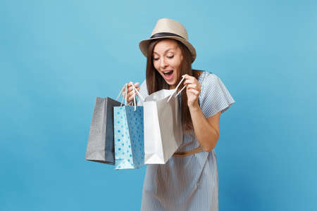 Portrait fashionable smiling beautiful caucasian woman in summer dress, straw hat holding packages bags with purchases after shopping isolated on blue pastel background. Copy space for advertisement Stock Photo