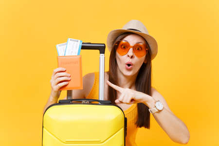 Fun tourist woman in summer casual clothes, hat, orange sunglasses with suitcase, passport isolated on yellow background. Passenger traveling abroad to travel on weekends getaway. Air flight concept