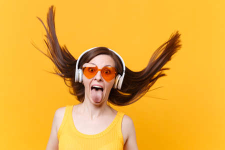 Portrait of excited cheerful laughter funny comic woman in orange glasses in headphones with fluttering hair isolated on yellow background. People sincere emotions lifestyle concept. Advertising area