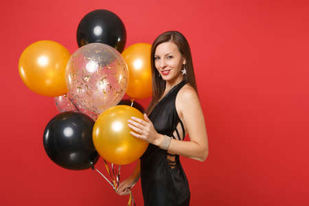 Stunning young girl in little black dress celebrating holding air balloons isolated on red background. St. Valentine's International Women's Day, Happy New Year, birthday mockup holiday party concept Imagens