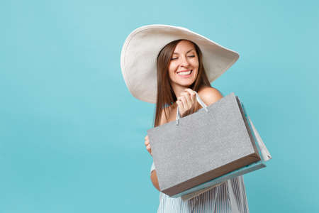 Portrait fashionable elegant fashion beautiful caucasian woman in summer dress, white large wide brim sun hat holding packages bags with purchases after shopping isolated on blue pastel background